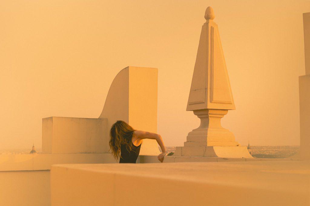 2020: fotografía, amigos y maestros. Imagen en color. Mujer en terraza de edificio. Se apoya con los brazos, hacia atrás, en la barandilla de cemento de la terraza.