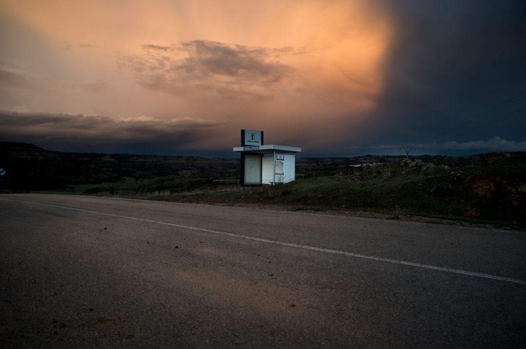 Imagen en color. Parada de autobús en una carretera desértica.