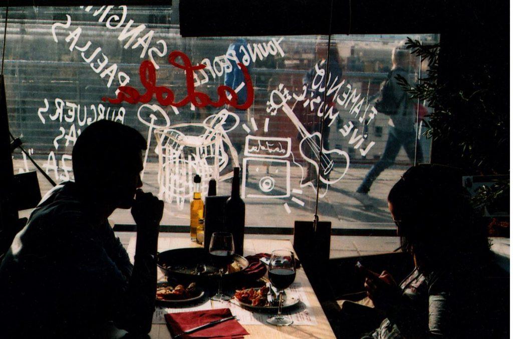 Imagen en color. Dos personas en  un bar, a contraluz, contra el cristal de la ventana que da a la calle y en el que se ven cosas escritas.