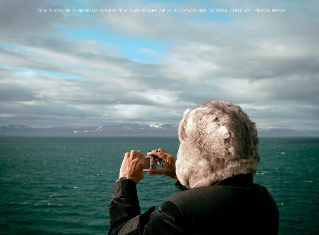 Imagen en color. Mujer con gorro de piel hace una foto, con una mini cámara, al mar.